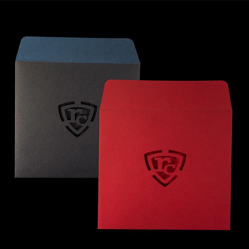 Квадратни пликове, червени и черни, с прав капак и изрязани инициали на лицето. Гладка цветна офсетова хартия, 120 г.